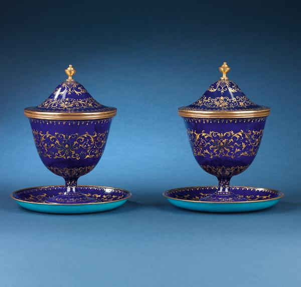 A pair of rare painted enamel covered cups and saucers